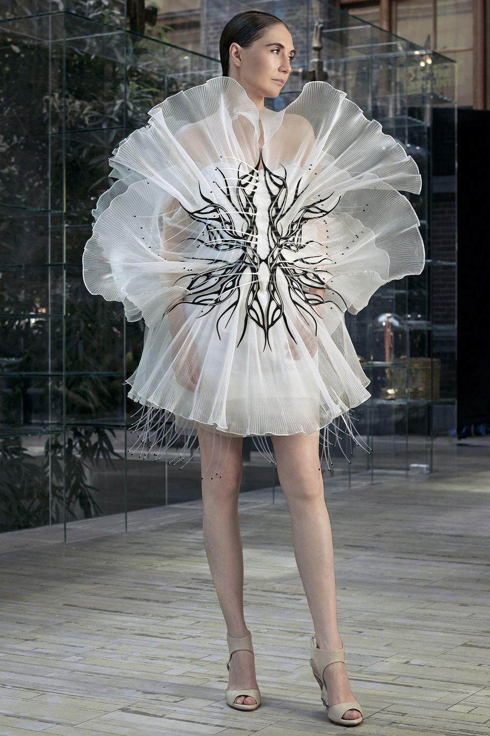 "<p>Iris van Herpen takes fashion to the next level, sourcing inspiration from artists who explore mathematics, technology, and symmetry in their oeuvres. And for the fall 2020 season, the Dutch designer is reinforcing this quality, creating a singular dress inspired by the work of Maurits Cornelis Escher, the celebrated graphic artist who counts Pulitzer Prize–winning scientists as fans. </p><p>Van Herpen specifically focuses on Escher's study on transformation and how reality can be warped through optics. In a film that stars <em>Game of Thrones</em> actress Carice van Houten, her hypothesis is put on full display: The white gauzy silk organza protrudes like petals from a bodice that features a sinuous black print, with the silhouette changing from different angles. And when hit with a strong light, the pleated material reveals more and more layers. There are also antennae sprouting from the hem, vibrating with every step. </p><p>It is as if the dress is an organic life form, functioning on its own and adapting to the environment that it's in. The design is a testament to van Herpen's calling card—one that marries nature and technology seamlessly.—<em>Barry Samaha</em></p><p><a class=""link rapid-noclick-resp"" href=""https://www.youtube.com/watch?v=aS4emRhmRHM"" rel=""nofollow noopener"" target=""_blank"" data-ylk=""slk:Watch Now"">Watch Now</a></p>"