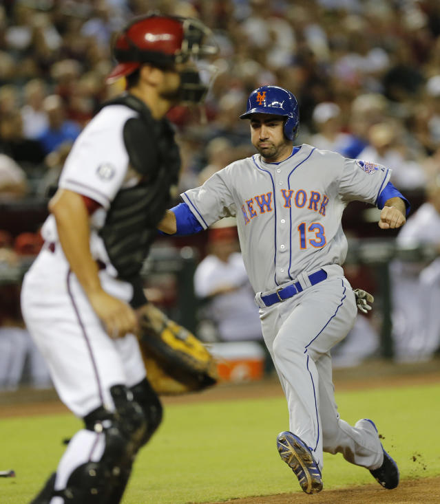 New York Mets' Josh Satin (13) scores on a base hit by teammate Justin Turner as Arizona Diamondbacks catcher Wil Nieves looks on during the fourth inning of a baseball game on Friday, Aug. 9, 2013, in Phoenix. (AP Photo/Matt York)