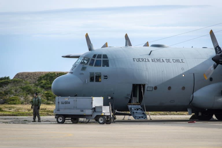 A man stands next to a C-130 plane that returned to Punta Arenas, Chile, from a search of the Drake Passage for a missing Air Force plane with 38 people aboard