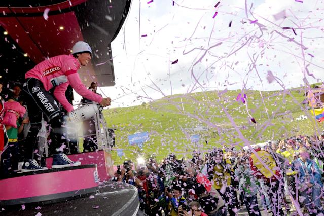 Colombia's Rigoberto Uran celebrates on podium after retaining the pink jersey of leader of the race during the 15th stage of the Giro D'Italia cycling race from Valdengo to Plan di Montecampione, Italy, Sunday, May 25, 2014. (AP Photo/Marco Alpozzi)