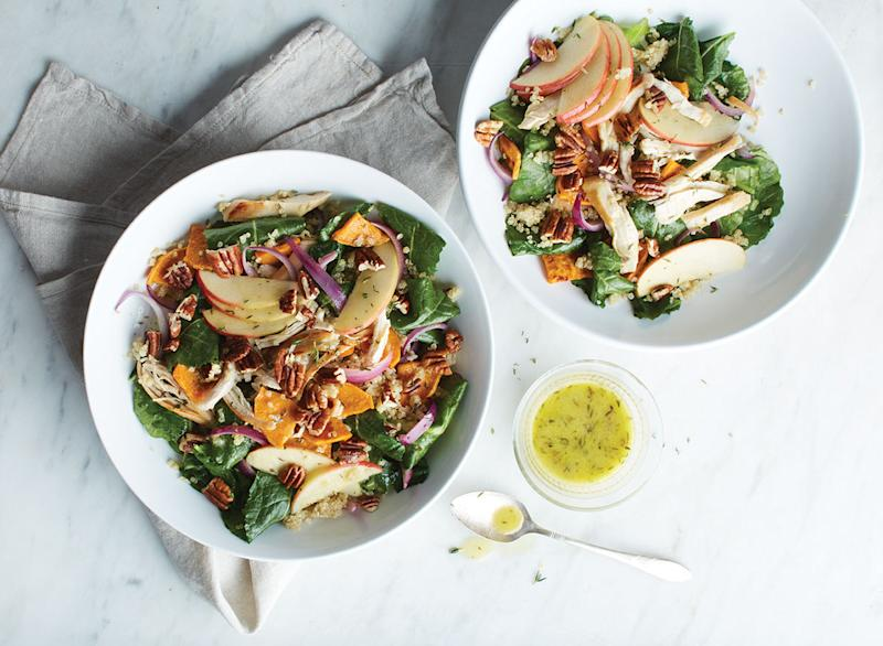 kale quinoa salad with apples and walnuts in two white bowls
