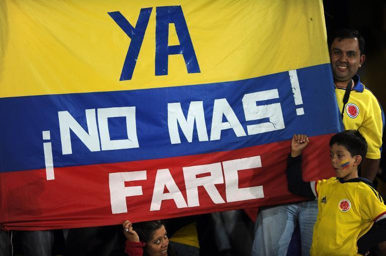 """Colombian fans hold a national flag reading """"No more FARC"""" before an Under-20 World Cup match against Costa Rica in Bogota, Colombia, on August 9, 2011"""