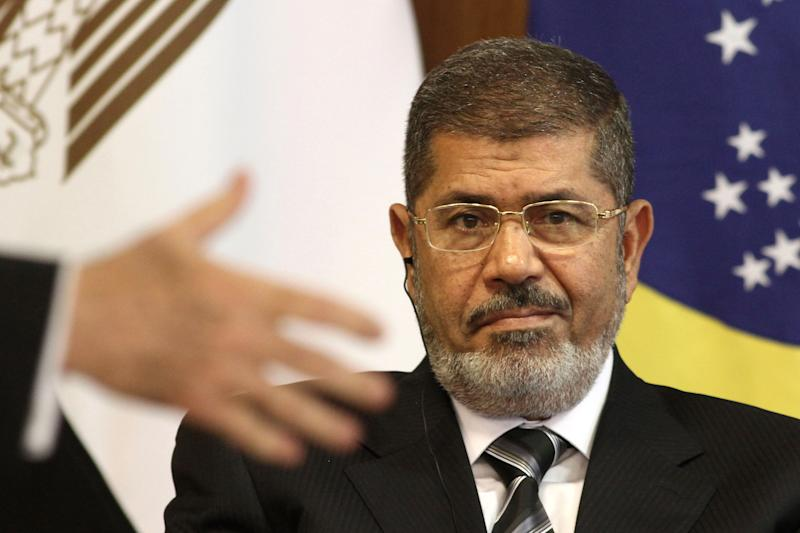 FILE - In this file photo taken Wednesday, May 8, 2013, Egyptian President Mohammed Morsi attends a bi-lateral signing ceremony with Brazil's president at the Planalto presidential palace in Brasilia, Brazil. An Egyptian court on Sunday, June 23, 2013, said Muslim Brotherhood members conspired with Hamas, Hezbollah and local militants to storm a prison in 2011 and free 34 Brotherhood leaders, including the future President Mohammed Morsi. (AP Photo/Eraldo Peres, File)
