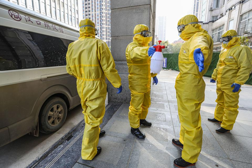 This photo taken on January 30, 2020 shows staff members of a funeral parlour wearing protective suits disinfecting a colleague after they transferred a body at a hospital in Wuhan in China's central Hubei province, during the virus outbreak in the city. - The World Health Organization declared a global emergency over the new coronavirus, as China reported January 31 the death toll had climbed to 213 with nearly 10,000 infections. (Photo by STR / AFP) / China OUT (Photo by STR/AFP via Getty Images)