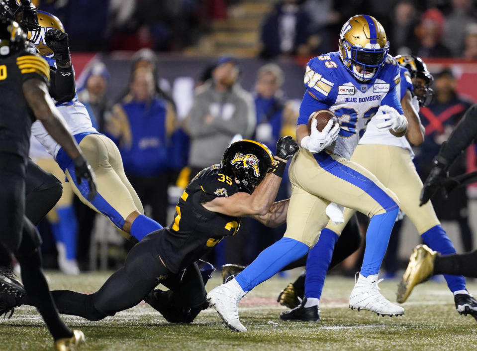 Andrew Harris #33 of the Winnipeg Blue Bombers attempts to break a tackle from Mike Daly of the Hamilton Tiger-Cats last year in the 107th Grey Cup Championship game. (Photo by John E. Sokolowski/Getty Images)