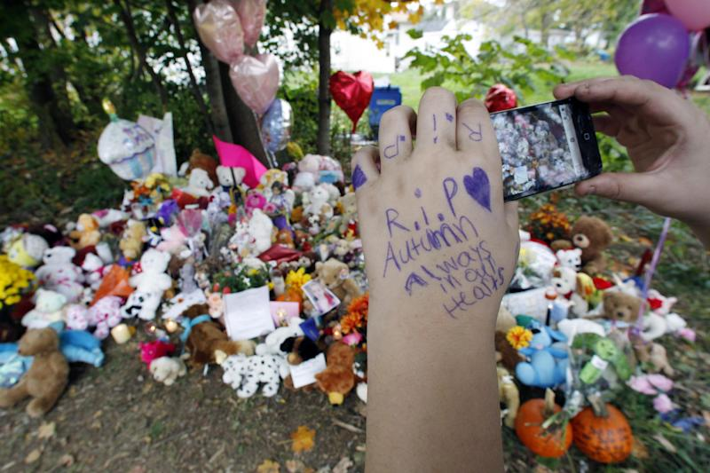 Autumn Pasquale's friend Vincent Kuehnl, 14, takes a photograph Thursday, Oct. 24, 2012 of the memorial shrine for Pasquale in Clayton,. N.J. near where the missing 12-year-old girl's body was found Monday in a home's recycling bin. Two teenage brothers were charged Tuesday with murdering Pasquale who had been missing since the weekend. (AP Photo/Mel Evans)