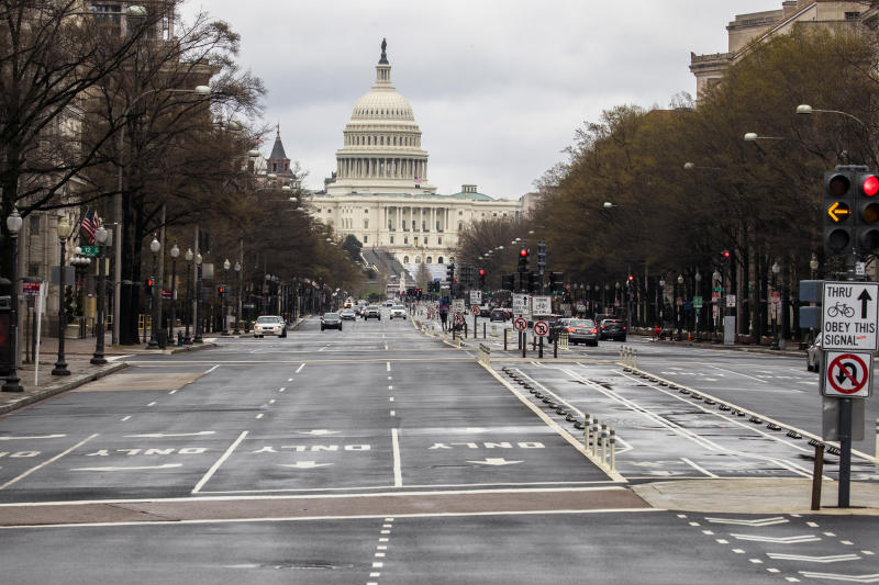 With the U.S. Capitol building in the background, motorists drive on Pennsylvania Avenue NW, Wednesday, March 25, 2020, in Washington. Officials have urged Washington residents to stay home to contain the spread of the coronavirus. (AP Photo/Manuel Balce Ceneta)