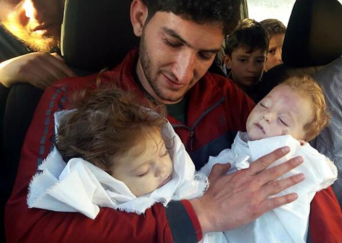 <p>In this picture taken on Tuesday April 4, 2017, Abdul-Hamid Alyousef, 29, holds his twin babies who were killed during a suspected chemical weapons attack, in Khan Sheikhoun in the northern province of Idlib, Syria. Alyousef also lost his wife, two brothers, nephews and many other family members in the attack that claimed scores of his relatives. The death toll from a suspected chemical attack on a northern Syrian town rose to 72 on Wednesday as activists and rescue workers found more terrified survivors hiding in shelters near the site of the harrowing assault, one of the deadliest in Syria's civil war. (Alaa Alyousef via AP) </p>