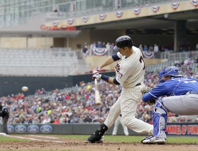 Minnesota Twins first baseman Joe Mauer (7) swings for a 3-run home run off Kansas City Royals pitcher James Shields during the second inning of a baseball game in Minneapolis, Saturday, April 12, 2014. At right is Royals catcher Salvador Perez. The Twins won 7-1.(AP Photo/Ann Heisenfelt)