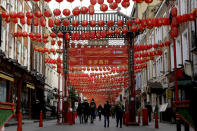 <p>People walk beneath lanterns hung across the street to celebrate the Chinese Lunar New Year which marks the Year of the Ox, in the Chinatown district of central London, Friday, Feb. 12, 2021. Chinese New Year celebrations were muted in London as England remains in its third national lockdown since the coronavirus outbreak began. (AP Photo/Matt Dunham)</p>