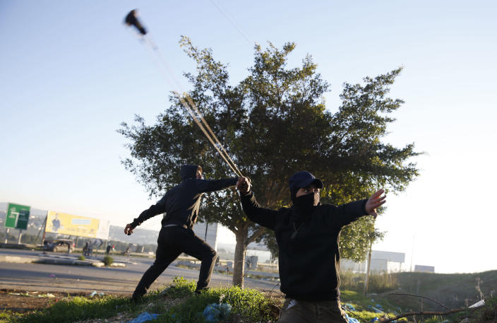 Palestinian protestor throws stones during clashes with Israeli troops at the Hawara checkpoint, south of the West Bank city of Nablus, Friday, Dec. 14, 2018. (AP Photo/Majdi Mohammed)