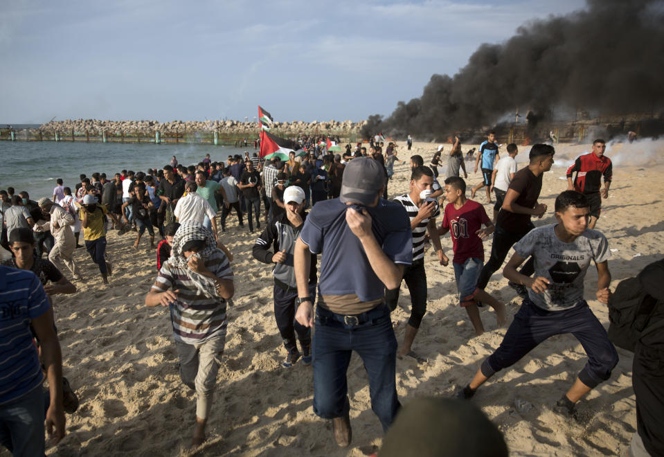 Palestinian protesters run for cover from teargas fired by Israeli troops during a protest on the beach at the border with Israel near Beit Lahiya, northern Gaza Strip, Monday, Oct. 15, 2018.(AP Photo/Khalil Hamra)