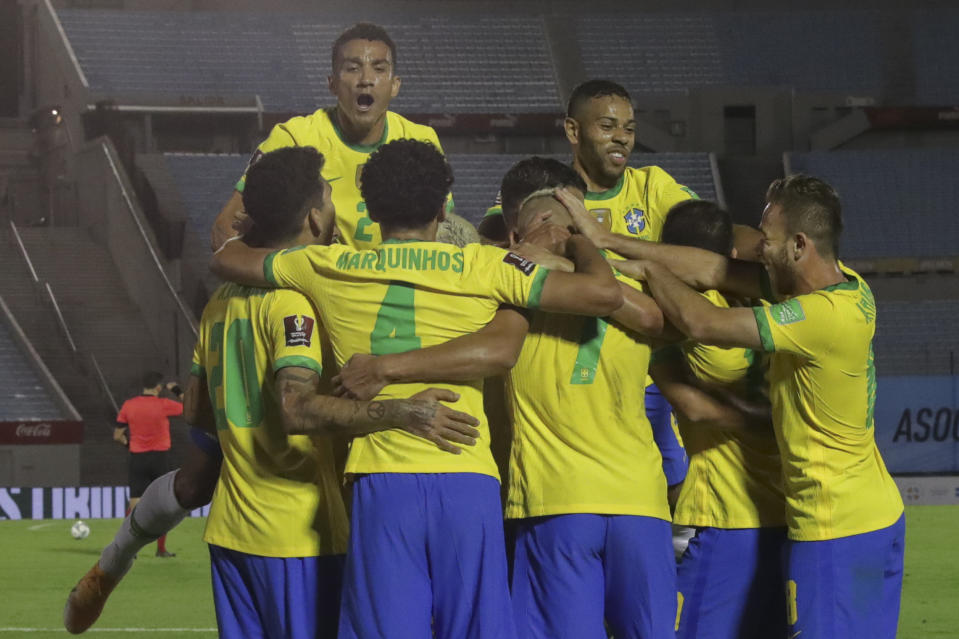 Brazil's Richarlison (C, back to camera) celebrates with teammates after scoring against Uruguay during their closed-door 2022 FIFA World Cup South American qualifier football match at the Centenario Stadium in Montevideo on November 17, 2020. (Photo by Raul MARTINEZ / POOL / AFP) (Photo by RAUL MARTINEZ/POOL/AFP via Getty Images)