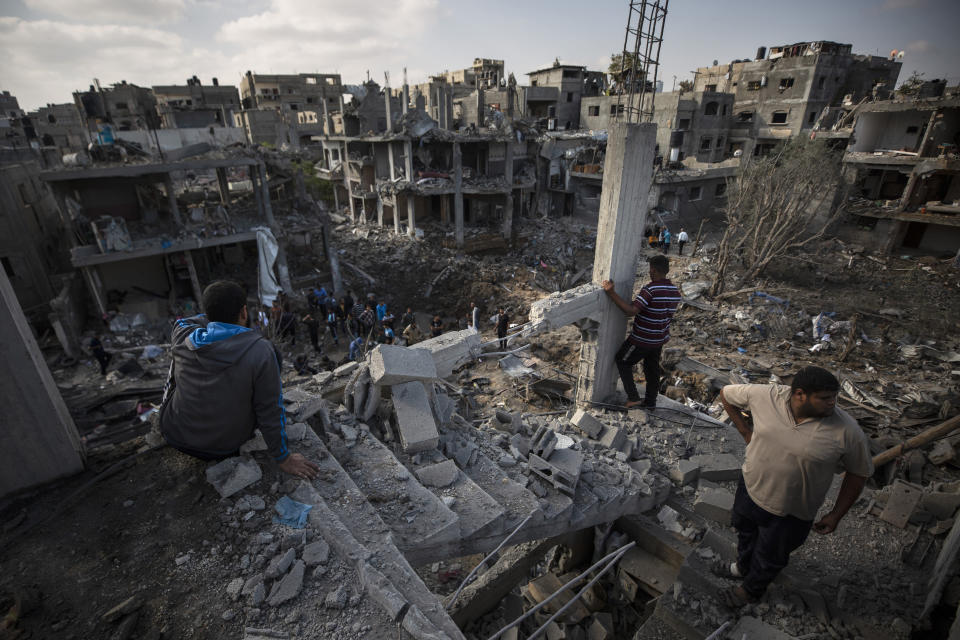 """FILE - In this May 14, 2021, file photo, Palestinians inspect their destroyed houses following overnight Israeli airstrikes in town of Beit Hanoun, northern Gaza Strip. Human Rights Watch on Tuesday, July 27, 2021, accused the Israeli military of carrying attacks that """"apparently amount to war crimes"""" during an 11-day war against the Hamas militant group in May. (AP Photo/Khalil Hamra, File)"""