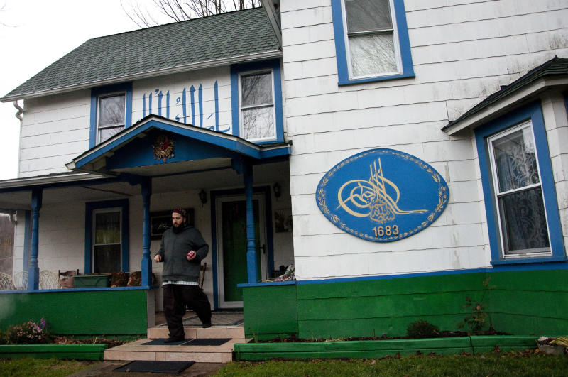 In this Nov. 5, 2010 photo, a disciple of the Osmanli Naksibendi Hakkani order exits the main residence of the dergah (Sufi center) in Sidney Center, N.Y. The town was thrust into the spotlight in summer 2010 after a controversy over the Muslim gravesites, bitterly dividing some residents while transforming others who say their lives and their town will never be the same. (AP Photo/Heather Ainsworth)