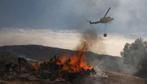 An helicopter flies over a fire in Bugarra, Spain