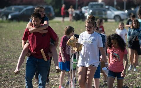 Evacuated students and staff march to buses to be carried offsite outside Noblesville West Middle School - Credit: Getty