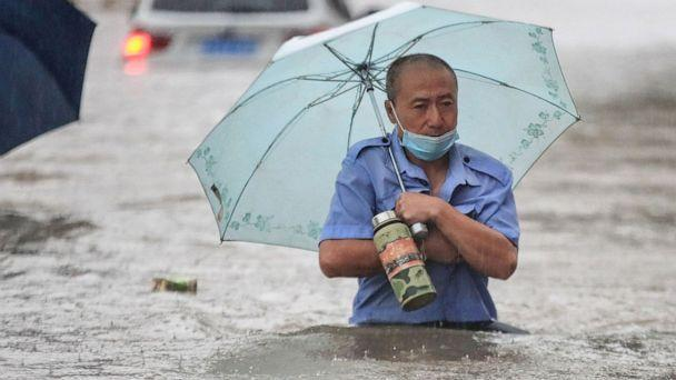 PHOTO: A man wading through flood waters along a street following heavy rains in China. (AFP via Getty Images)