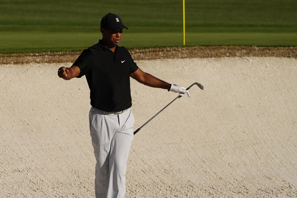 Tiger Woods reaches after his bunker shot on the second hole during the second round of the Masters golf tournament Friday, Nov. 13, 2020, in Augusta, Ga. (AP Photo/Matt Slocum)
