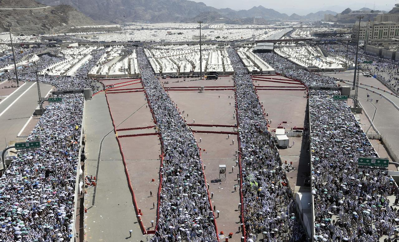 """A crowd of Muslim pilgrims make their way to throw stones at a pillar, symbolizing the stoning of Satan, in a ritual called """"Jamarat,"""" a rite of the annual hajj, in Mina near the Saudi holy city of Mecca, Saudi Arabia, Sunday, Oct. 28, 2012. (AP Photo/Hassan Ammar)"""