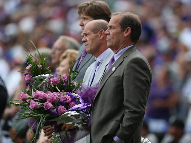 From front, Colorado Rockies co-owners Dick and Charlie Monfort hold bouquets of flowers for presentation to Christy Helton, wife of retired Rockies first baseman Todd Helton, as the team's chief operating officer, Greg Feasel, looks on during a ceremony to retire Helton's number before the Rockies host the Cincinnati Reds in a baseball game in Denver on Sunday, Aug. 17, 2014. (AP Photo/David Zalubowski)