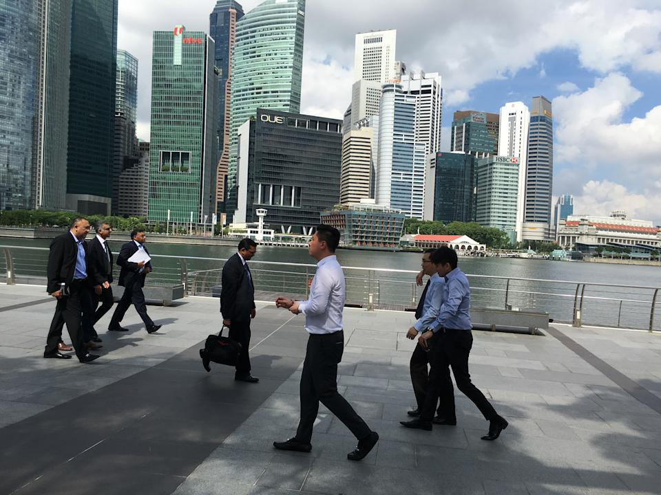 Businessmen walk along the Marina Bay financial district of Singapore on Thursday, Jan. 14, 2016. Singapore, which is about the size of New York City, has a population of more than 5 million and its economy relies mainly on finance, tourism and manufacturing. (AP Photo/Wong Maye-E)