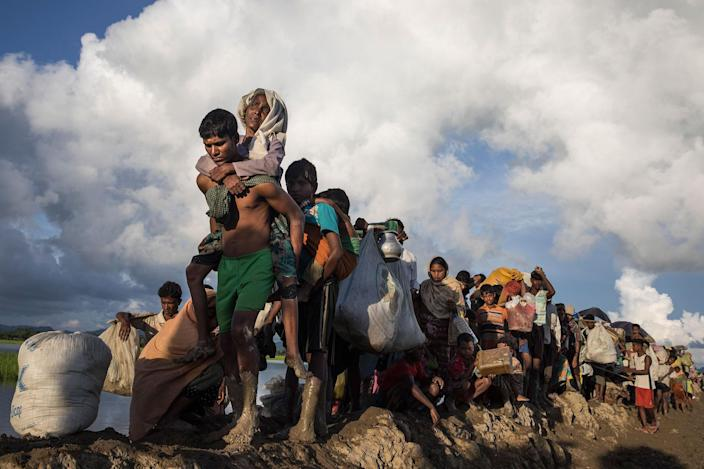Thousands of Rohingya refugees fleeing from Myanmar walk along a muddy rice field after crossing the border in Palang Khali, Cox's Bazar, Bangladesh, on Oct. 9, 2017. (Photo: Paula Bronstein/Getty Images)
