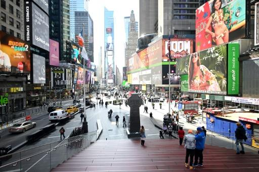 Few people are seen at Times Square in Manhattan on March 16, 2020 in New York City