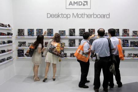 FILE PHOTO: Visitors look at motherboards being displayed at the AMD booth during the 2012 Computex exhibition at the TWTC Nangang exhibition hall in Taipei June 6, 2012. REUTERS/Yi-ting Chung/File Photo