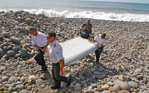 <span>French police officers carry a piece of MH370 debris from a plane in Saint-Andre, Reunion Island, near Madagascar in 2015</span> <span>Credit: AP/Lucas Marie </span>