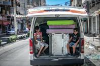 Palestinian children sit in a van loaded with salvaged belongings from their home at the Al-Jawhara Tower in Gaza City, on Monday