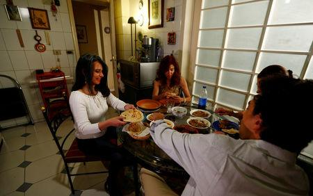 Maha Ragaay eats with her family and friendes as they break their fast near a picture of Jesus, in her home in the Cairo suburb of Maadi, Egypt, April 14, 2017. REUTERS/Amr Abdallah Dalsh