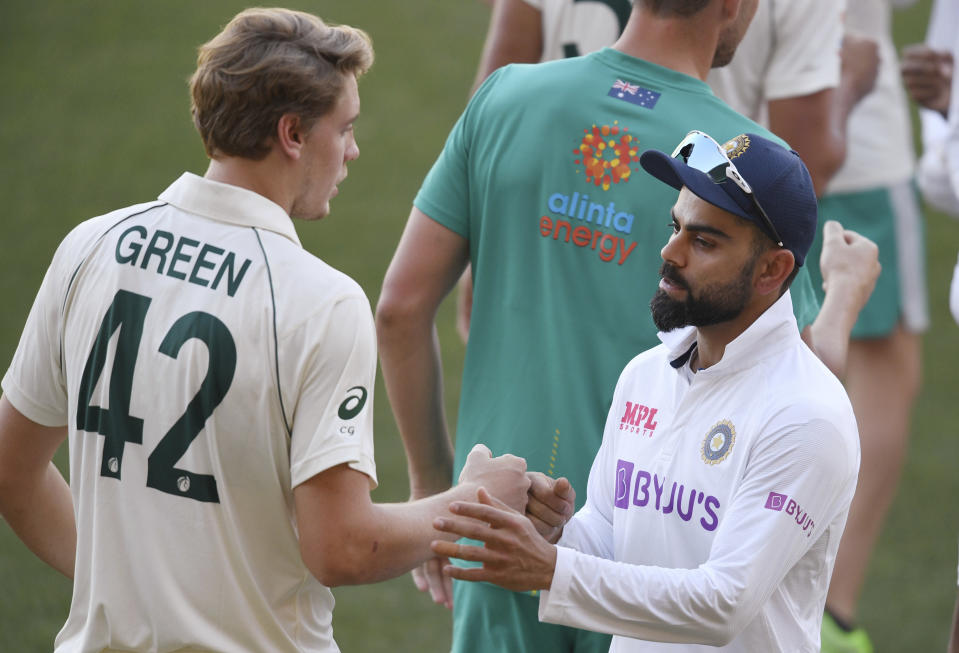 India's Virat Kohli, right, shakes hands with Australia's Cameron Green after Australia won on the third day of their cricket test match at the Adelaide Oval in Adelaide, Australia, Saturday, Dec. 19, 2020. Australia won the match. (AP Photo/David Mariuz)