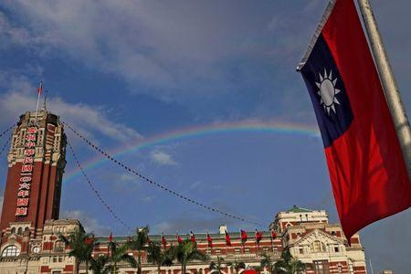 A rainbow is seen behind Taiwanese flag during the National Day celebrations in Taipei