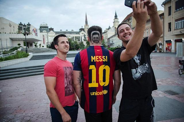 Selfies with a football fan sporting a hair 'tattoo' of Argentinian superstar Lionel Messi in Novi Sad, Serbia, on June 10 (AFP Photo/VLADIMIR ZIVOJINOVIC)