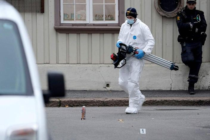 A police forensic officer carries material during investigations after the shootings (NTB/AFP via Getty Images)
