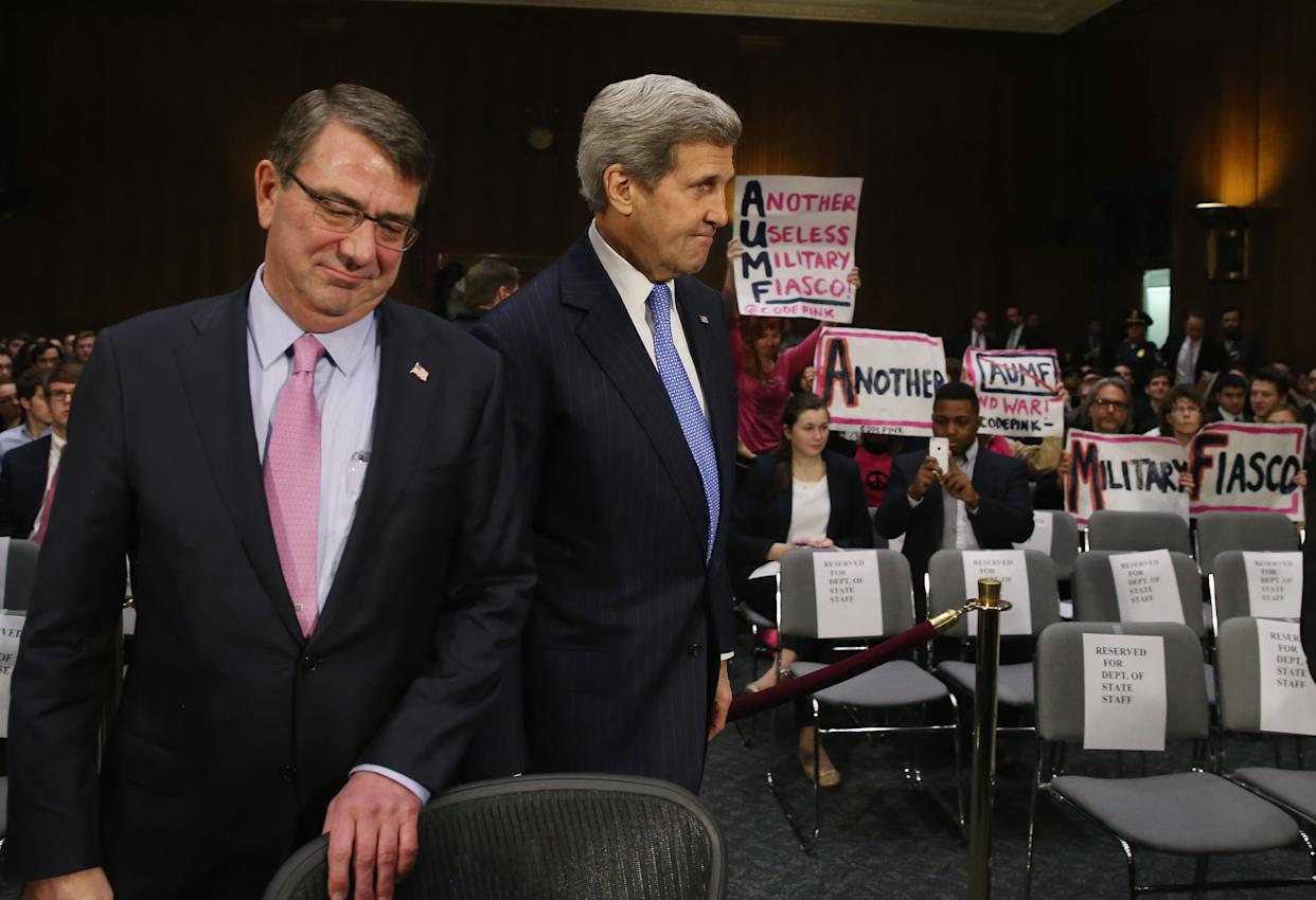 Protesters from Code Pink hold up signs as Secretary of State John Kerry and Defense Secretary Ashton Carter arrive to testify before the Senate Foreign Relations Committee on Capitol Hill on March 11, 2015.