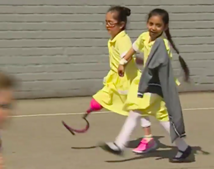 One little girl walked hand in hand with Anu around the school playground (BBC)