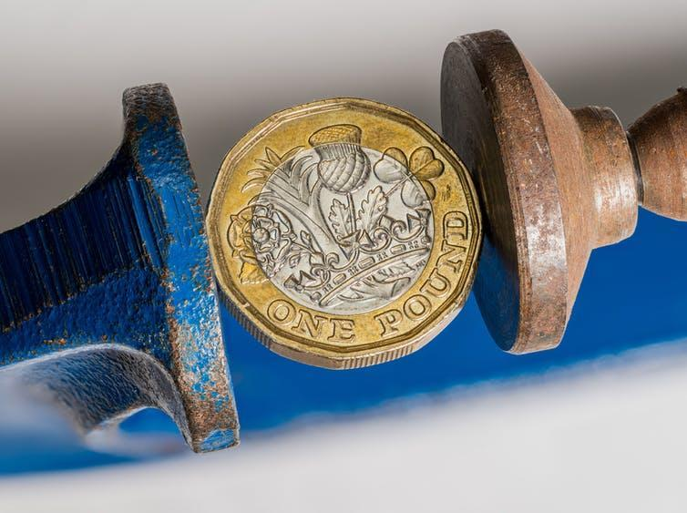 Pound coin being squeezed in a vice