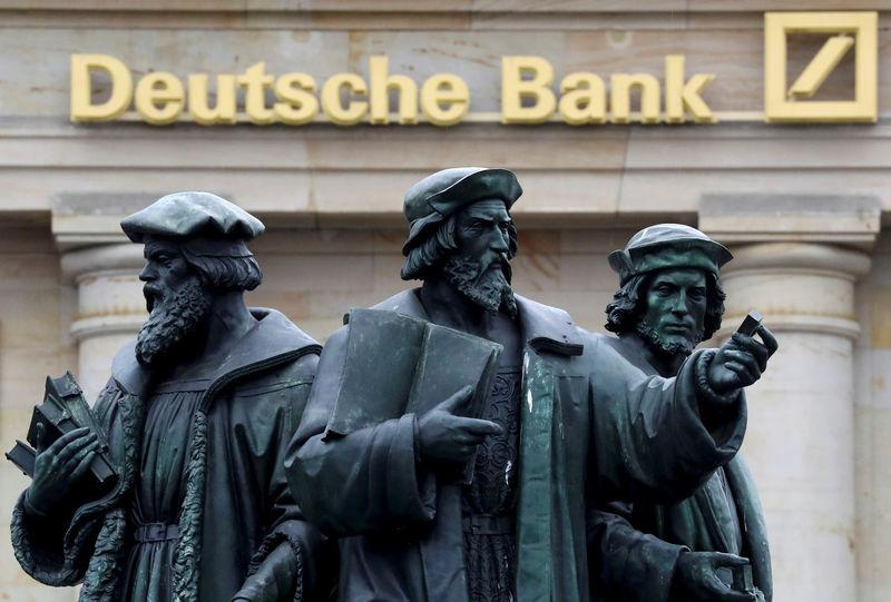 FILE PHOTO - A statue is pictured next to the logo of Germany's Deutsche Bank in Frankfurt