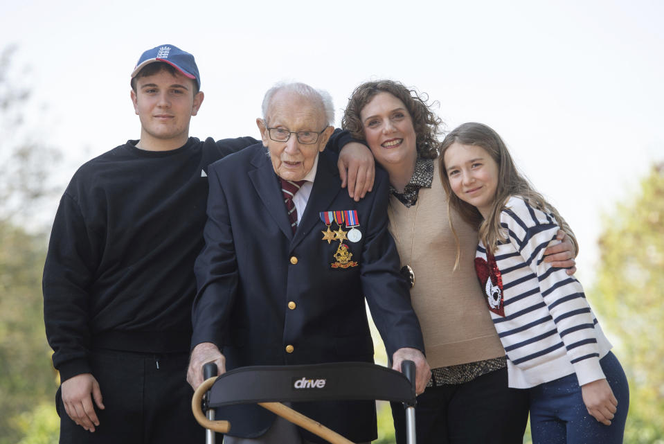 99-year-old war veteran Captain Tom Moore, poses with family members, from left, grandson Benji, daughter Hannah Ingram-Moore and granddaughter Georgia, at his home in Marston Moretaine, England, Thursday April 16, 2020, after he achieved his goal of 100 laps of his garden. (Joe Giddens/PA via AP)