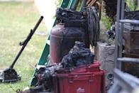 A burned tank is seen in the garden of a suburban home that was the site of a hash oil extraction laboratory explosion in the Mira Mesa area of San Diego