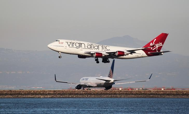 A Virgin Atlantic Boeing 747-400 lands as a United Airlines Boeing 767 taxis at San Francisco International Airport, San Francisco