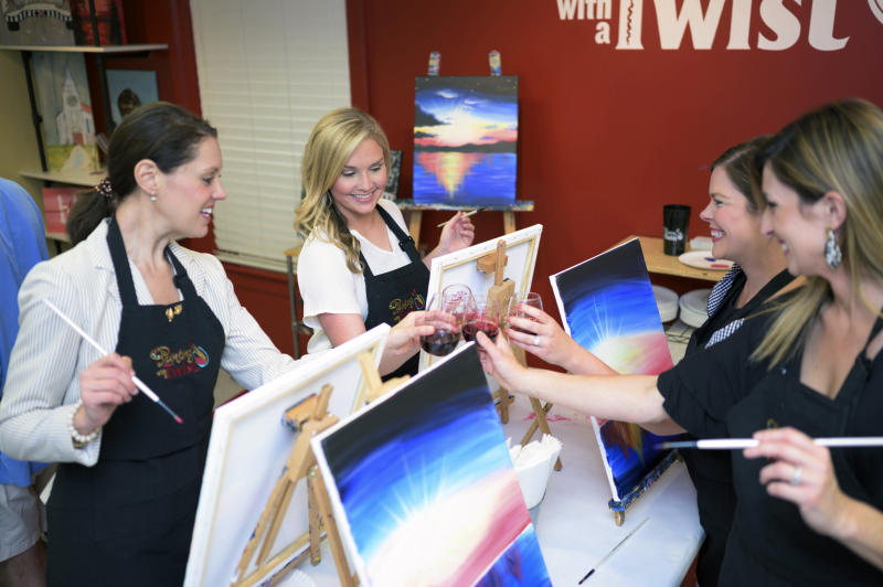 This 2019 photo provided by Painting with a Twist shows a group of women during a Painting with a Twist event in Mandeville, La. In recent years, the interactive painting industry has become a global sensation. Around the world, adults can spend their nights out learning to paint in a relaxed, BYOB setting. Thousands of franchises exist to help us all unleash our inner creative. (Painting with a Twist via AP)