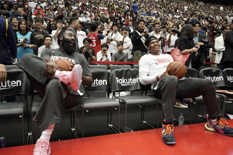 Houston Rockets' James Harden, left, and Russell Westbrook share a light moment during warmups for the team's NBA preseason basketball game against the Toronto Raptors Thursday, Oct. 10, 2019, in Saitama, near Tokyo. (AP Photo/Jae C. Hong)