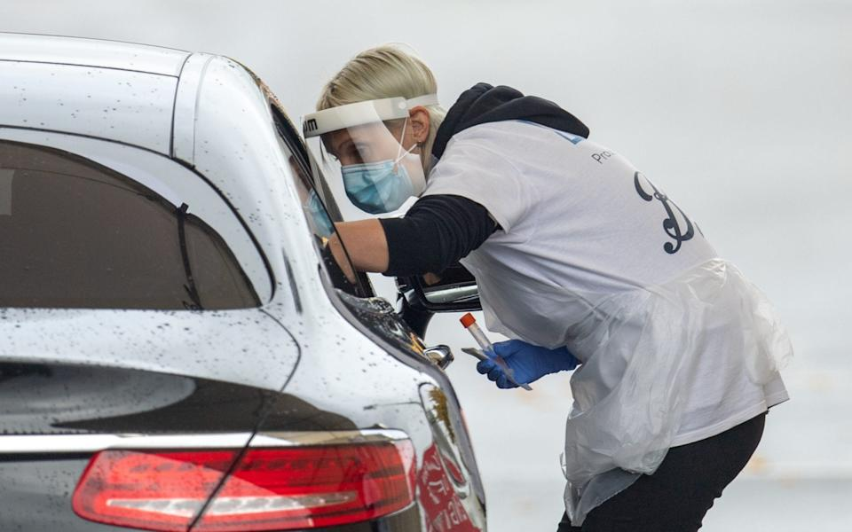 Staff collect samples at a drive through test centre in Leicester. A new three-tier system of alert levels for England has been implemented following rising coronavirus cases and hospital admissions - Joe Giddens/PA Wire