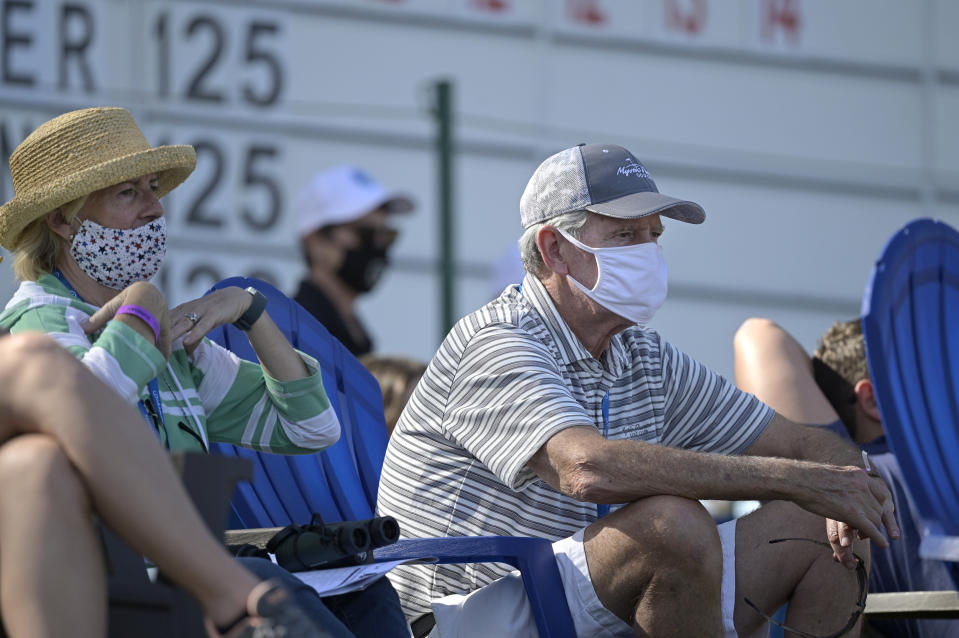 Spectators wear masks while watching along the 18th green during the final round of the Tournament of Champions LPGA golf tournament, Sunday, Jan. 24, 2021, in Lake Buena Vista, Fla. (AP Photo/Phelan M. Ebenhack)
