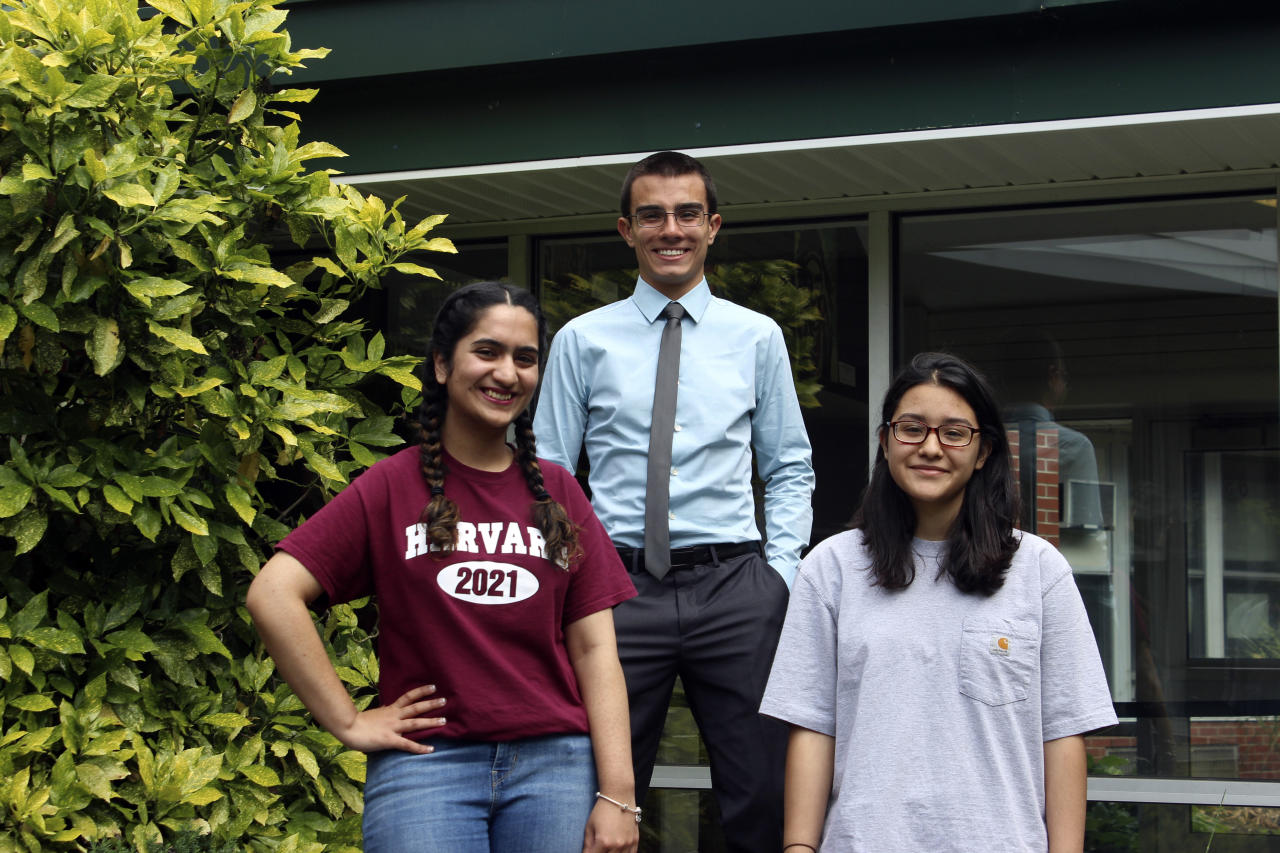 In this photo taken Thursday, June 15, 2017, in Brentwood, N.Y., high school valedictorians Reeda Iqbal, left, Michael Simoes, center, and co-salutatorian Saray Vazquez pose at the high school. The students are graduating after a year that saw several gang killings in their Long Island community, including five victims who attended Brentwood High School. (AP Photo/Frank Eltman)