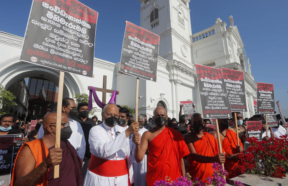"""Cardinal Malcolm Ranjith, archbishop of Colombo, second left, along with Buddhist monks and other Catholic devotees hold placards during a protest demanding justice for the 2019 Easter Sunday bomb attack victims out side the St. Anthony's church, one of attack sites, in Colombo, Sri Lanka, Sunday, March 7, 2021. Placards read, """"Easter Sunday Massacre, Who ran the operation behind the curtain"""" (AP Photo/Eranga Jayawardena)"""