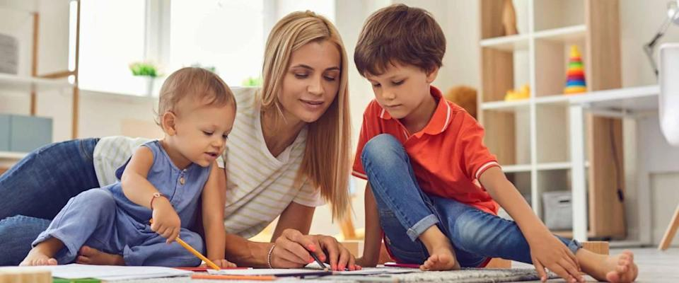 Young mother and little children drawing picture together sitting on floor.
